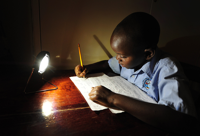 Christopher_from_Zambia_studying_by_the_light_of_a_solar_lamp